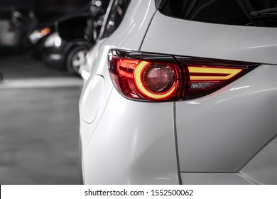 Close up detail on one of the LED  white taillight modern white crossover car. Exterior detail automobile.