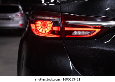 Close up detail on one of the LED black taillight modern red crossover car. Exterior detail automobile.
