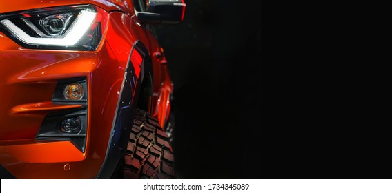 Close up detail on one of the LED headlights red Pickup Truck on black background