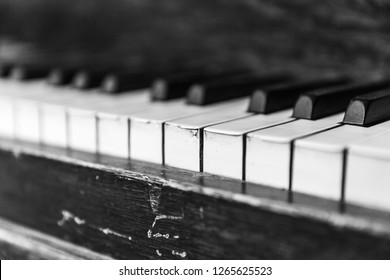 Close up detail of piano keyboard on an old upright piano (black and white / monochrome photo).
