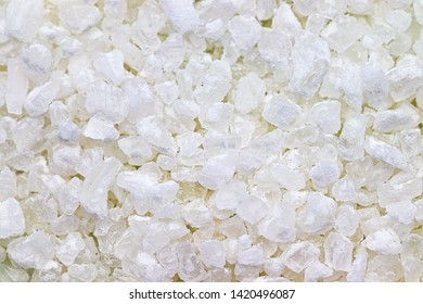 close up detail of a pile of big grains of white coarse salt on a white background