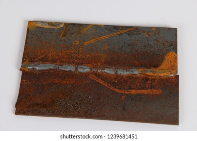 Close up detail of a poor and weak MIG weld on mild steel plate. Old and rusty