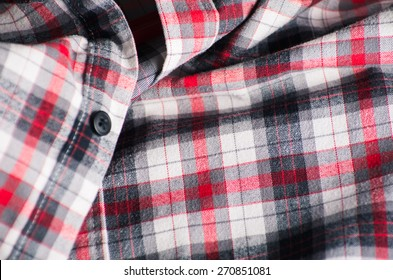 Close up detail of a red plaid button up style shirt.