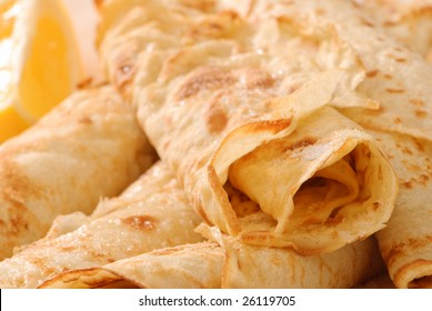Close up detail of rolled up pancakes with lemon