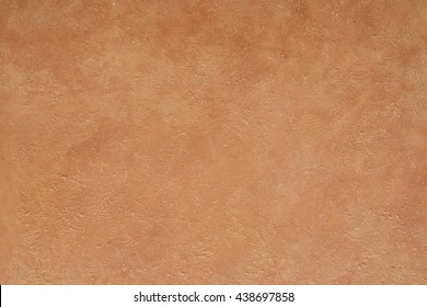 close up detail of rustic textured terracotta coloured stucco wall background