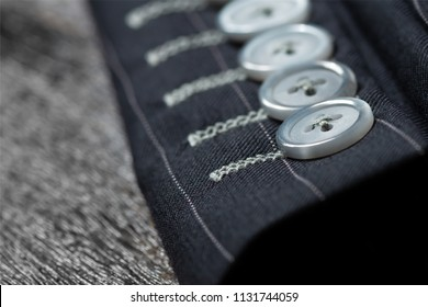 Close up detail of sleeve  buttons and stitching for custom made jacket on old wooden table, professional tailor concept.Bespoke jacket. Pay attention in every details.