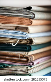 Close Up Detail of Stack of Folded Fabrics in Variety of Colors, Patterns, and Textures in Textile Shop
