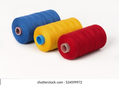 Close up detail still life of blue yellow red spools of thread isolated on white background copy space - concept fashion DIY clothing sewing handicraft design handmade textile tradition