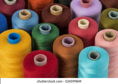 Close up detail still life of colorful red yellow green blue brown spools of thread isolated on white background copy space - concept fashion DIY clothing sewing handicraft design handmade tradition