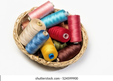 Close up detail still life of colorful spools of thread in basket on white background isolated on white background copy space - concept fashion DIY clothing sewing handicraft handmade tradition