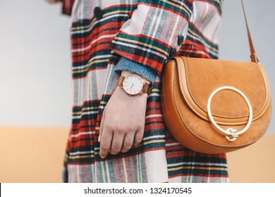 Close up detail of stylish young woman wearing a coat with chequered pattern and a wrist watch while holding a fancy yellow bag in front of a multicolored background.