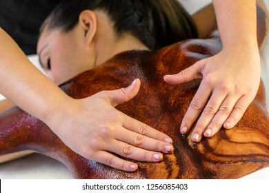 Close up detail of therapist doing hot antioxidant chocolate back massage on young woman.