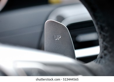 close detail of the upshift paddle in a luxury sportscar