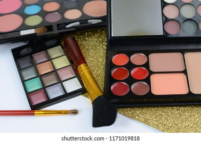 Close up detail of a variety of colorful cosmetics. Samples are messy. Samples include eyeshadows, blushed and lip glass. There is a sparkly gold mat underneath