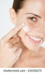 Close up detail view of an attractive young woman applying hydrating care cream on her face with her finger, joyfully smiling at the camera against a white background, indoors.