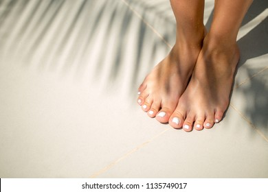 Close up detail view of bare tanned female feet with white pearl pedicure on white sand with a palm tree shadow. Travel and holiday lifestyle.