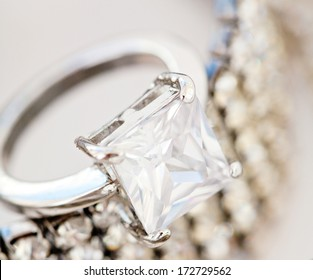 Close up detail view of a choice of quality female jewelery laying together on a white background and shining ring, bracelet and necklace. Luxury fashion jewels engagement ring.