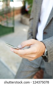 Close up detail view of an elegant businessman hand holding and using a smart phone outdoors.