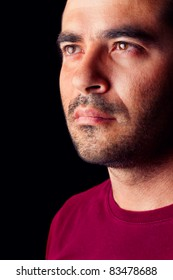 Close detail view of a young male man with a serious look isolated on a black background.