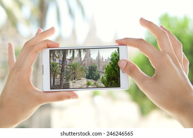 Close up detail view of a young tourist woman hands holding a smartphone mobile cell device, taking pictures of a monument while sightseeing on a holiday trip. Travel and technology outdoors.