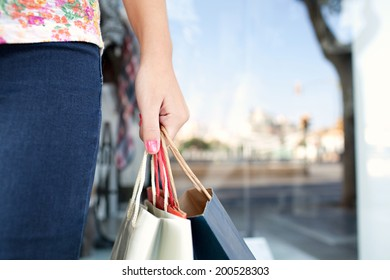 Close up detail view of a young woman middle section and hand holding paper carrier bags in a shopping mall with glass windows and city reflections during a sunny day. Consumer outdoors lifestyle.