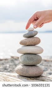Close up detail of woman's hand balancing a stack of beach stones on a driftwood log. Balance, relaxation, meditation, nature, peaceful, zen lifestyle concepts.