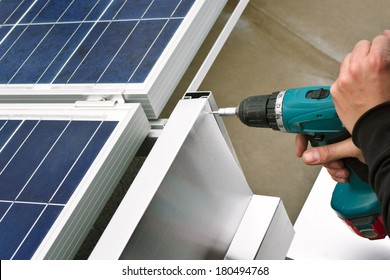 Close up detail of worker with electrical drill or borer installing windbreaker on solar panel construction on a flat roof.