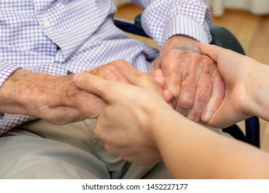 Close up detail of young female caregiver holding hands with old man in wheelchair.