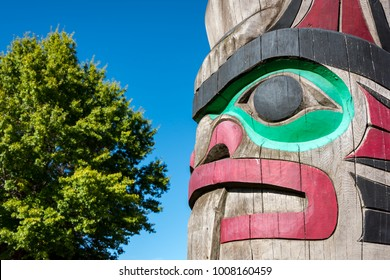 Close up detailing of ancient colorful Totem pole with blue sky behind it in Duncan, British Columbia, Canada.