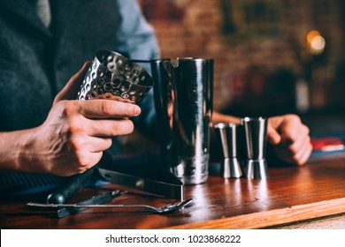Close up details of barman hands using cocktail tools. Professional bartender working at bar