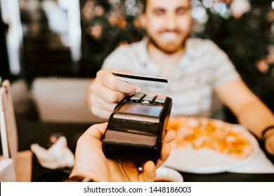 Close up details of contactless credit card payment at restaurant