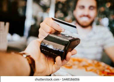 Close up details of contactless credit card payment at restaurant. Hand of customer paying with contactless credit card with modern technology.