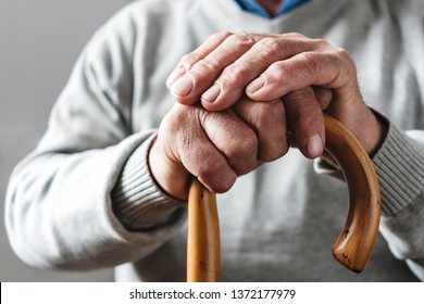 Close up details of the folded hands of an elderly man resting on a walking cane in a mobility and health concept