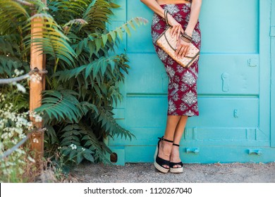 close up details of footwear sandals on a wedge of stylish beautiful woman posing on blue background, summer style, fashion trend, skirt, skinny, straw handbag, accessories, tropical vacation, legs
