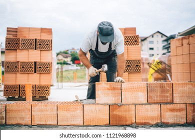 Close up details of industrial bricklayer installing bricks on construction site