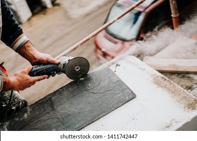 Close up details of industrial worker cutting stone marble with angle grinder at construction site