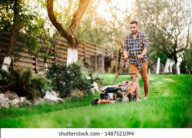 Close up details of landscaping and gardening. Worker using industrial manual lawnmower