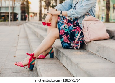 close up details of legs in pink sandals of woman sitting on stairs in city street in stylish printed skirt with leather backpack holding sunglasses, summer style trend