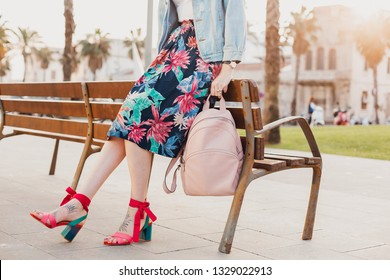 close up details of legs in pink sandals of stylish woman walking in city street in printed colorful skirt, holding pink leather backpack, summer style footwear trend