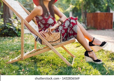 close up details legs wearing wedges sandal shoes, footwear. stylish beautiful woman sitting in deck chair in tropical style outfit, summer fashion trend, holding straw handbag