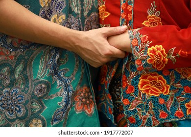 Close up details shot of southeast Asian man and woman in traditional Malay batik and kebaya dress, holding hands.