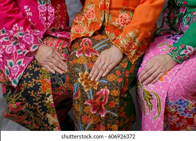 Close up details shot of southeast Asian woman in traditional Malay batik kebaya dress.