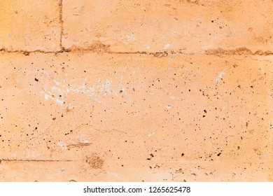 Close up details of stone or masonry on the side of a building. Cracks and imperfections of concrete stone work.