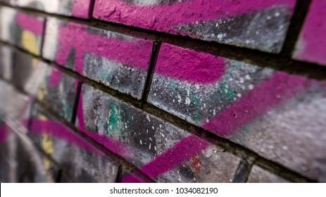 Close up details of urban art sprayed purple line of graffiti on old brick wall macro image