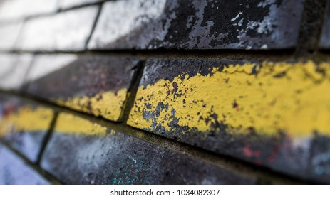 Close up details of urban art sprayed yellow line of graffiti on old brick wall macro image