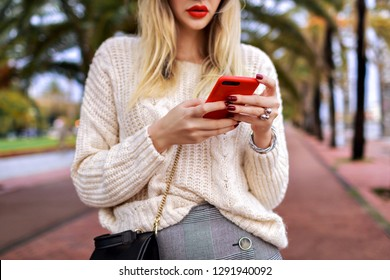 Close up details of woman posing in the street and tap on her smartphone, red lips and cozy trendy white sweater, student fashion.