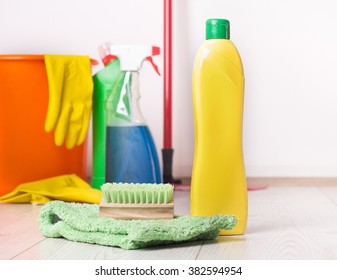 Close up of detergent bottle, mop and brush on the bright wooden floor and other cleaning supplies and equipment in background