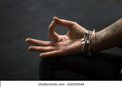 Close up of Dhyana (Gyan or Jnana) Mudra, spiritual hand gesture performed with yogi female fingers, tattoo and wrist bracelets. Woman meditating on black mat background. Meditation session concept