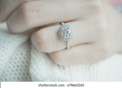 Close up Diamond ring on woman's finger before wedding with white scarf background.(soft and selective focus)