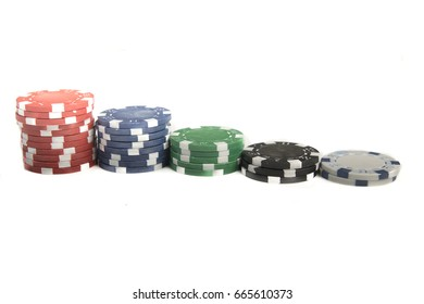 Close up of different coloured gaming chips in a row of decreasing sized piles.